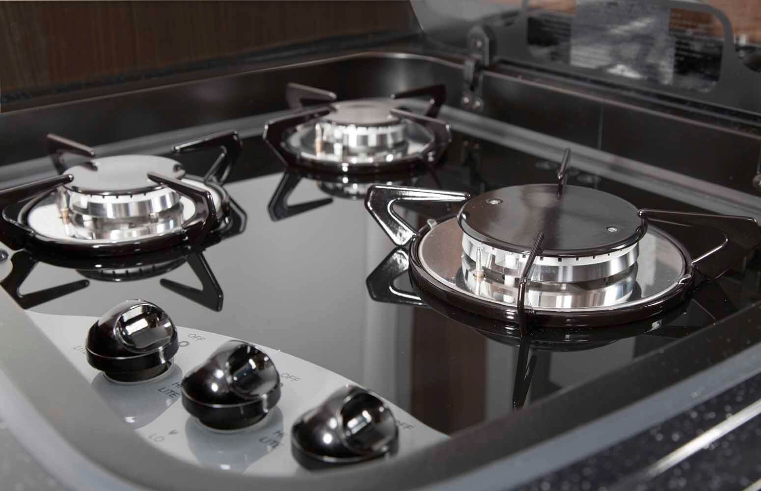 Massive gas stove with powerful burners and glass-covered steel surface